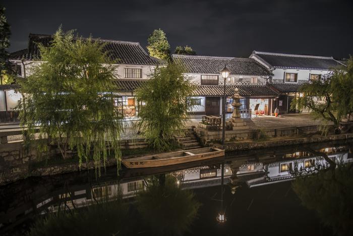 夜の美観地区は、大勢の観光客で賑わう日中とは異なる表情を見せてくれます。レトロな街頭が放つやさしい灯り、灯りに照らされた柳の樹々、闇夜に浮かび上がる白壁となまこ壁の屋敷、倉敷川の水面が鏡のように屋敷の数々を映し出す様が織りなし、美観地区は幻想的な雰囲気に包まれます。