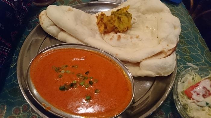 当店の人気は、やはり北インド料理ならではの、チキンやマトンを使った濃厚なカレーや、ナン、タンドゥーリチキンといったタンドール窯を用いた焼き物料理。  一番の人気は、この店ならではの『バターチキンカレー』。チキンは柔らかくしっとり。マイルドな味わいで、甘味もあり、美味しいと評判です。【ナンやライス、サラダがセットになった『日替わりのバターチキンカレー』】