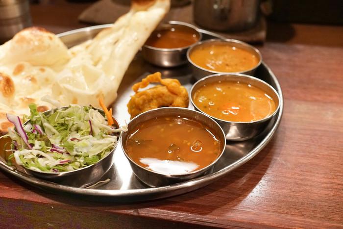 """経験豊富なシェフが作る「ダクシン」の料理は、インドの伝統的な健康法""""アーユル・ヴェーダ""""の思想を取り込んだもの。スパイスをたっぷりと使った料理は、低カロリーで健康的。ハラルミートを用い、野菜料理も充実しているので、ムスリムの方も、ベジタリアンの方もしっかりと食事を楽しむことが出来ます。  【日替わりカレー2種、サンバル、ラッサム、ナン、パスマティライス、サラダ 等などがセットになった『Dセット』は、平日ランチメニューの一つ。】"""