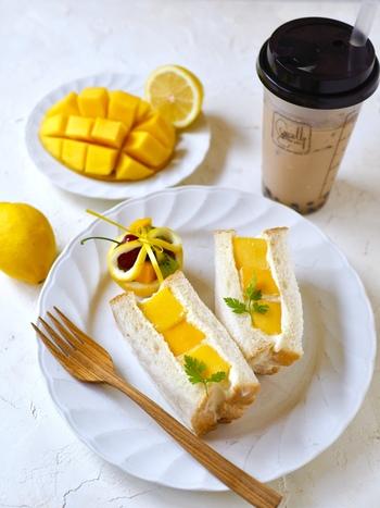 生クリームにクリームチーズを加えた、チーズクリームとマンゴーのフルーツサンドです。マンゴーの鮮やかな黄色が食欲をそそります。