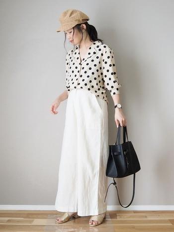 レトロな印象のドット柄シャツには、白のワイドパンツを合わせて上品な着こなしに。ヌーディカラーのサンダルやキャスケットで全体を統一させて大人っぽくまとめたスタイルです。