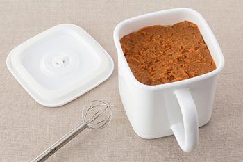 """中でも「持ち手付ストッカー」は取っ手付きなので、「塩麴・醤油麹」などの頻繁に使う調味料の保存にもぴったりのアイテムです。冷蔵庫から出す時にも取っ手があることでスムーズに出し入れでき、""""密閉蓋""""を合わせれば、長期保存も安心です。""""密閉蓋""""の中央にはつまみがあり、引き上げると蓋が開き、下げると密閉されます。さらに""""密閉蓋""""の裏側にシリコンゴムが付いているので、汁やにおい漏れを防いでくれます。"""