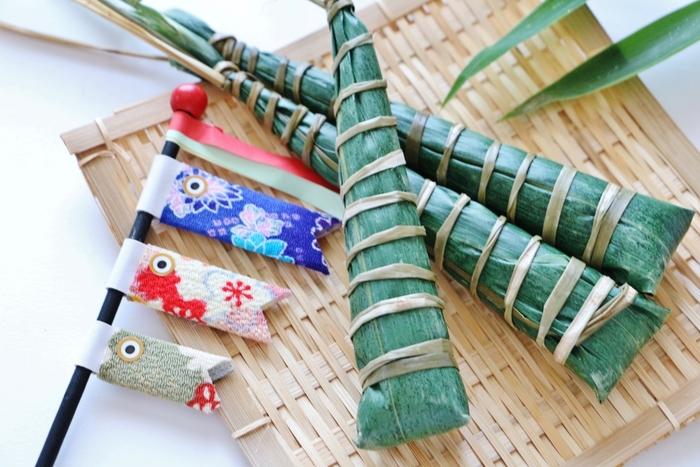 ちまきの由来は約2300年前の中国から来ています。当時の楚の愛国者だった詩人の屈原が、入水自殺をした後、彼の死を悲しんだ人々が、命日の5月5日に米を詰めた竹筒を投じて供養していました。しかし、川に住む竜に食べられてしまうため、竜が竜が嫌う葉で米を包んで、赤・青・黄・白・黒の五色の糸で縛ったものを、川に流すようになったそう。