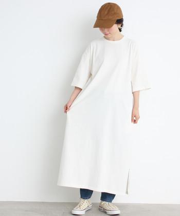 ロング丈の白Tシャツワンピースに、デニムパンツとスニーカーを合わせたベーシックなコーディネート。ブラウンのキャップでアクセントをプラスして、ラフだけどトレンド感を盛り込んだ着こなしに仕上げています。