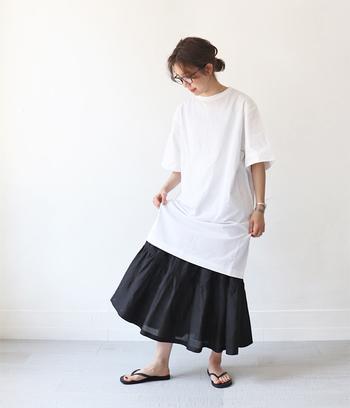 白のシンプルTシャツワンピに、黒のボリューミーなスカートを合わせたコーディネート。ベーシックなアイテム同士を組み合わせたモノトーンコーデは、大人のくつろぎスタイルにもぴったりです。足元はトングサンダルで、季節感もしっかりアピール♪