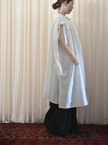 ゆったり着こなせる白のノースリーブワンピースに、黒のロングスカートを合わせたコーディネートです。無地アイテム同士の組み合わせで、シンプルなモノトーンコーデに。リラックス感のあるワイドシルエットが、大人のゆとりを感じさせるスタイリングです。
