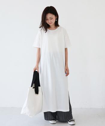 マキシ丈のTシャツワンピースに、ストライプ柄のワイドパンツを合わせた着こなしです。スニーカーやトートバッグも白×黒の組み合わせでそろえて、カジュアルなモノトーンコーデに仕上げています。
