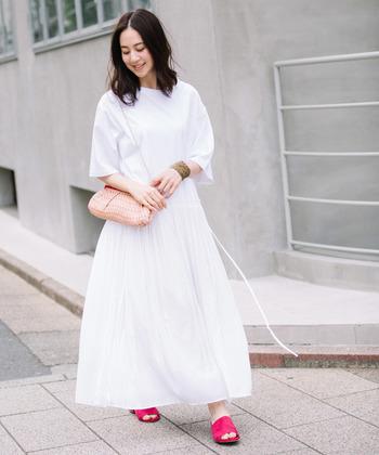 Tシャツとプリーツスカートを組み合わせた、異素材切り替えの白ワンピース。一枚で着るだけでサマになるアイテムは、シンプルに着こなすのがおすすめ。差し色の赤いサンダルが素敵ですね。