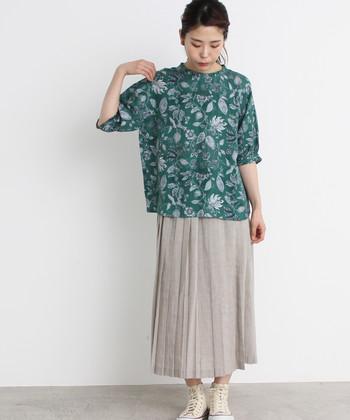 グリーンの花柄トップスに、グレーのプリーツスカートを合わせた大人っぽさを意識したコーディネートです。控えめな雰囲気になり過ぎないよう、足元はハイカットの白スニーカーでカジュアルダウンしているのがポイント♪