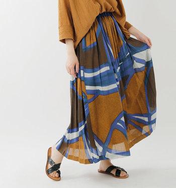 コットン100%の薄手で軽く、動きやすいロング丈スカートです。大胆にジオメトリック柄をプリントし、落ち着いたカラーなのに印象的なデザインに仕上げています。白や黒のシンプルトップスを合わせてもいいですが、同系色のブラウントップスでセットアップ風にコーディネートしても◎