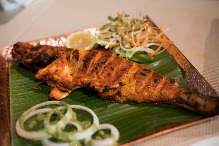 """インド料理は、これまで北と南という分類で大雑把に紹介されてきましたが、「バンゲラズキッチン」が、異彩の放つのは、南インドの一地方である""""バンガロール""""の料理に特化したことです。  アラビア海を西に接する「マンガロール」は、古くから王朝の港町と栄えた都市。歴史的建造物が残る当都市は、インドの""""食の都""""として古くから有名です。  【店では、サワラやマナガツオ、カレイやイカ等など、市場から仕入れた新鮮な魚介類を食材として豊富に用いる。画像は、スズキを丸ごと一匹用いた『スズキ まるごとタンドール』。】"""