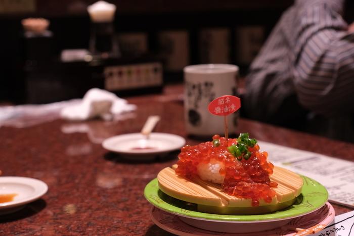 ◆「回転寿司 根室花まる」◆ リーズナブルに函館の海鮮を!という方は、回転寿司の人気店「回転寿司 根室花まる」がおすすめ。JR函館駅から3分程度歩いたところにある商業施設「キラリス函館」の地下一階にあります。中に入ると活気があって、ワクワクしますよ。カジュアルな雰囲気なので、お子様のいるご家庭でも安心して入れるのがうれしいですね。  こちらは、筋子のしょうゆ漬け。イクラのつぶつぶがたっぷりですね。