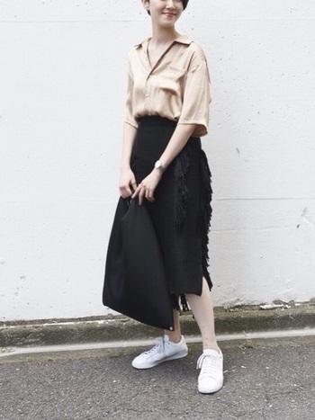 ベージュのオープンカラーシャツを黒のタイトスカートにインして、幅広のシルエットを女性らしく着こなしています。光沢感のある素材を選ぶだけで、カジュアルになりすぎない大人コーデに。