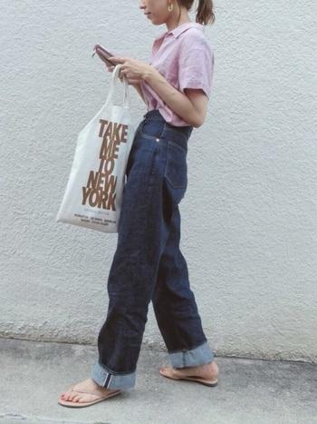ハイウエスのストレートデニムにピンクの半袖シャツをインしたカジュアルスタイル。ボーイッシュな中に甘さをひとさじ。濃紺のデニムの裾をロールアップし、ヌーディーなフラットサンダルと合わせることで足元に抜け感を演出しています。