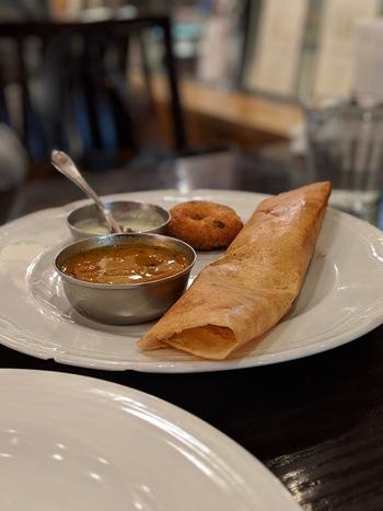 """記事を参考に、「東京駅」周辺で、印象深いスパイシーな舌の旅もぜひ満喫して下さい。  【「アーンドラ・ダイニング 銀座」のセットメニュー『アーンドラ・ドーサ・ミールス』の一部。ドーサ、ワダ、ココナツのチャツネ、サンバルがのった第一プレート。 ※ドーナッツ状の""""ワダ""""は、南インド特有の料理で、スパイス入りの小麦粉と豆の生地を揚げたもの。甘くはなく、ココナッツチャツネやサンバルと食べるのが一般的。】"""