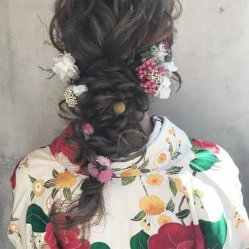 イマドキで華やかな印象にしたいなら、編み込みを重ねたゴージャスな編み下ろしヘアがぴったりです。一見複雑ですが、三つ編みを3本作り、それをまた三つ編みするだけで完成します。あえて小花のアクセサリーにすることで、メリハリのあるへアになりますよ。