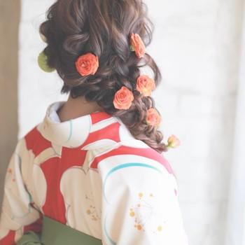 たっぷり編み込みを取り入れたサイド編み下ろしヘアに、華麗なバラの飾りを散りばめれば、誰もが目を引く華やかヘアに。振袖にも似合うヘアです。アクセサリーではなく、生花を使うのも素敵です。