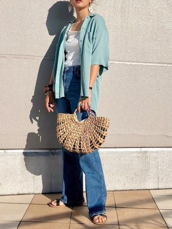 ペールブルーのオープンカラーシャツとデニムパンツの爽やかな着こなし。白の大ぶりピアスやかごバッグで、夏らしさを添えています。