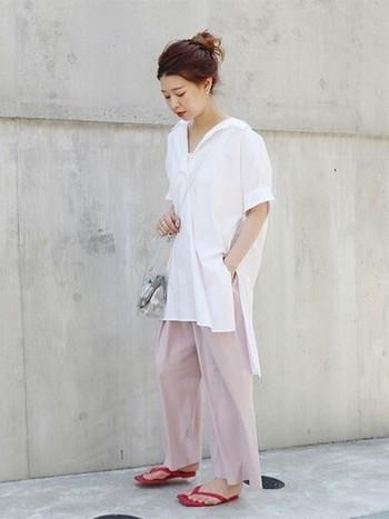 チュニック丈の白のスキッパーシャツに淡いピンクのワイドパンツを合わせた、大人リラックスなコーディネート。赤のトングサンダルを差し色に、クリアバッグで涼しさをプラスして。