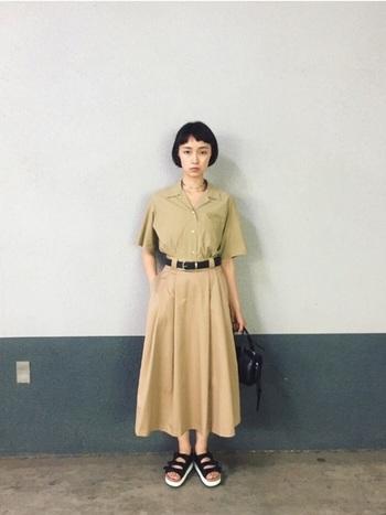 メンズライクなベージュの開襟シャツを同系色のフレアスカートにインして、ワンピース風に見せた着こなし。黒の小物で引き締めた、大人のサファリ風スタイルです。