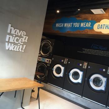 """スウェーデンブランド、エレクトラックスの洗濯機が設置されています。ランドリースペースに描かれた""""have a nice Wait!""""の文字もスタイリッシュ。"""