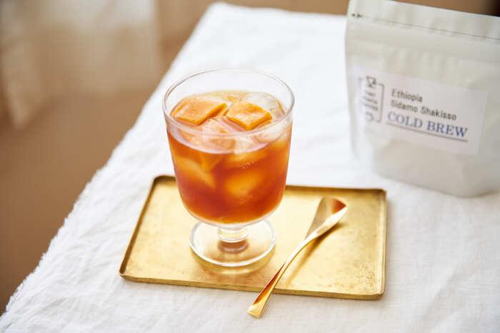 水出しコーヒーを淹れる際に、フルーツを一緒に加えて抽出する方法が「フルーツコールドブリュー」です。普通は「アイスコーヒーの豆」というと苦味の強い深煎りが適していると思われがちですが、こちらは、紅茶を思わせるほど香り高く浅煎りに仕上げたエチオピアの「シャキッソ」を使用。ドライマンゴーを一緒に入れることで、よりフルーティーで甘味のある味わいになります。
