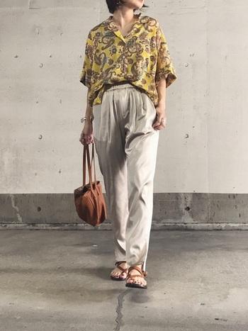 ペイズリー柄の開襟シャツに、光沢感のあるパンツを合わせたラグジュアリーなスタイリング。フロントをラフにインすることでこなれた印象に。ブラウンのレザーアイテムで上品にまとめています。
