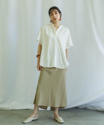 スキッパーシャツの首元とスカートのバックスリットや上下の裾のラインがさり気なくリンクしたコーディネート。素足にスリッパサンダルで、程よい抜け感を演出して。