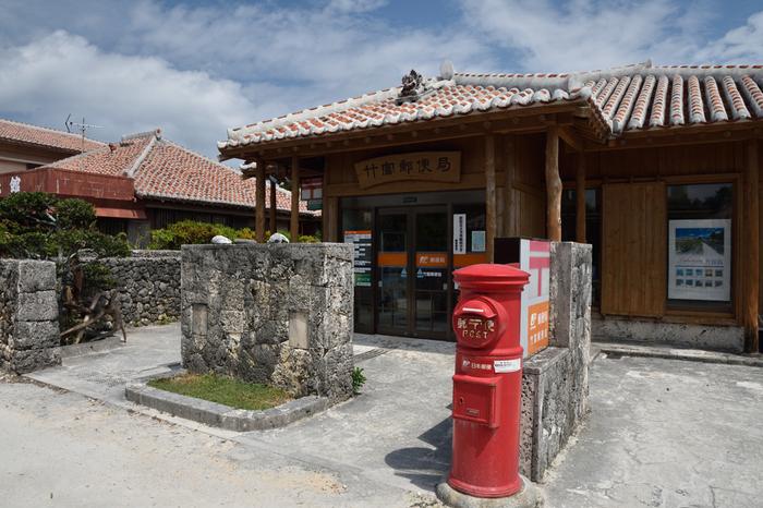 集落内にある竹富郵便局は、島内にある唯一の金融機関です。民家と同じ赤瓦屋根の平屋、屋根の上に乗ったシーサー、昔ながらの円筒形のポストがとても可愛らしく、のんびりとした佇まいの竹富島集落とよく調和しています。ここで郵便物を出すときは、係員にお願いすると、赤瓦屋根の家や星砂がデザインされた風景印を押してもらうことができます。記念に絵ハガキなどを送ってみるのもおすすめですよ。