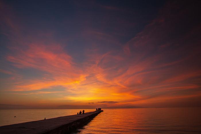 西桟橋で眺める夕焼けの美しさは格別です。夕陽の光を浴びて紅く染まった雲、藍色に変わりつつある空、夕陽の残光を映し出す海が融和した景色は、絶景そのものです。