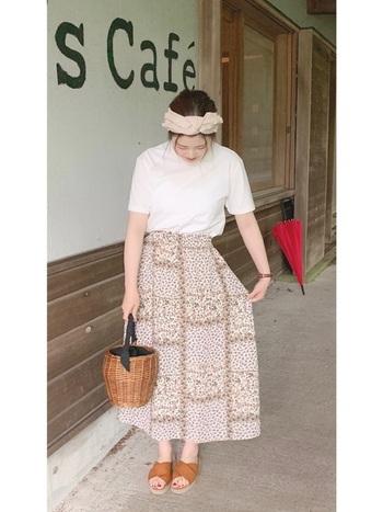 パッチワーク風のフラワースカートには、シンプルな白Tシャツを合わせてすっきり着こなすのが◎小物をベージュ系にすると、やさしげな雰囲気にまとまりますね。