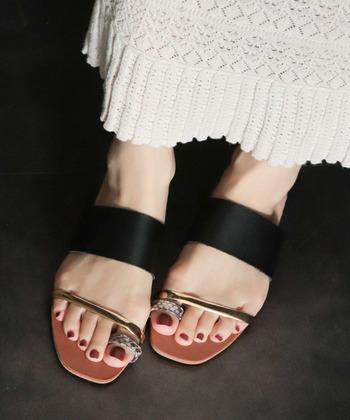 白いニットスカートには、黒×ゴールド×パイソン柄の大人なサンダルをON。ネイルもダークトーンの赤みがかったカラーにして、全体をシックな雰囲気にまとめています。