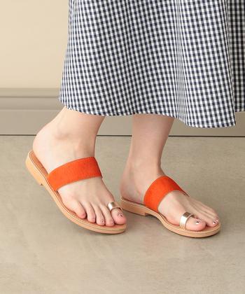 ギンガムチェックのスカートには、ベーシックになりすぎないようにビビッドなオレンジのサンダルを合わせて。ネイルはサンダルのパーツカラーorギンガムチェックのカラーとリンクさせて統一感を出しましょう。