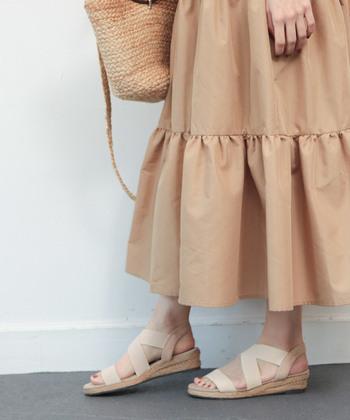オレンジがかったベージュのスカート地に、ベージュのかごバッグ、サンダルを合わせた夏のお嬢さん風コーデ。ただ可愛いだけじゃ物足りないので、ブラウンとレンガ色がミックスしたような絶妙カラーのネイルをポイントに。