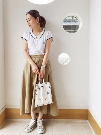 白ポロシャツもこんな風に裾部分に縁取りがあればぼんやりせずメリハリのある印象になります。ベージュのスカートとスニーカーのナチュラル感がリンクした、風通しの良いすっきりとしたスタイルです。