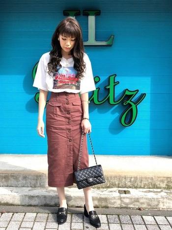 写真がプリントされたボーイッシュなTシャツに、タイトスカートをあわせた女性らしいコーデ。小物にブランド物をひとつ加えるだけで、上品さも加わります。
