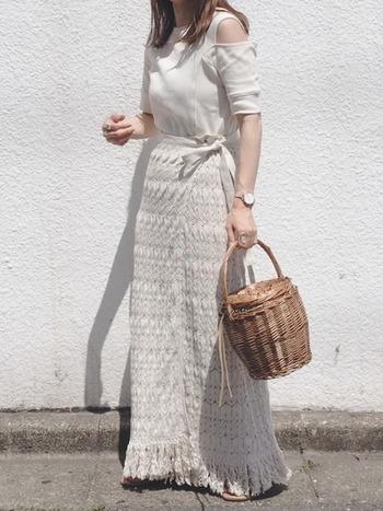 肩がチラ見えするカッティングがおしゃれなデザインTシャツは、レースのラップスカートやかごバッグでリゾート感を出したコーデに。ホワイト&淡いベージュのワントーンで大人っぽくヘルシーな印象になっています。