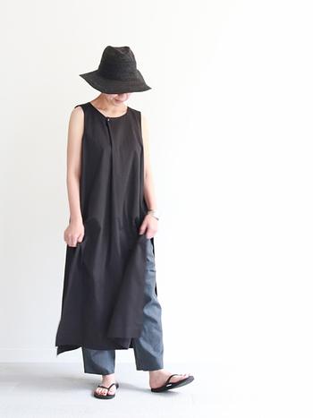 ウエストの下あたりにスリットが入ったデザインの、黒のノースリーブワンピース。ダークトーンのパンツやスカートを重ねて、スリットを楽しむ着こなしがおすすめです。あえて派手色のボトムスを、ちらりと覗かせても◎。