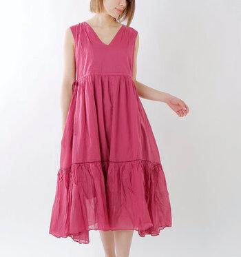 ひざ下丈でカジュアルな印象を与える、ピンクのノースリーブワンピース。ボリューム感のあるティアードデザインで、パンツとのレイヤードスタイルと相性抜群なアイテムです。サイドにあしらわれたリボンで、シルエットの調節が可能。