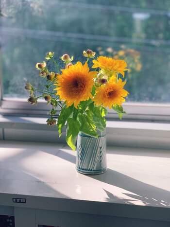 窓辺に飾ったひまわりは、陰影を落として、すこし大人っぽい雰囲気に仕上がりました。ふんわりとしたフォルムを大切にして、上品な快活さを演出しています。