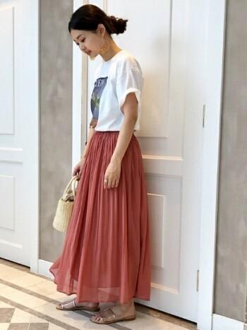透け感のあるマキシスカートにオレンジを取り入れたスタイリング。オレンジを主役に、そのほかのアイテムを白やベージュなどのナチュラルカラーで合わせるとぐっと大人な印象に◎