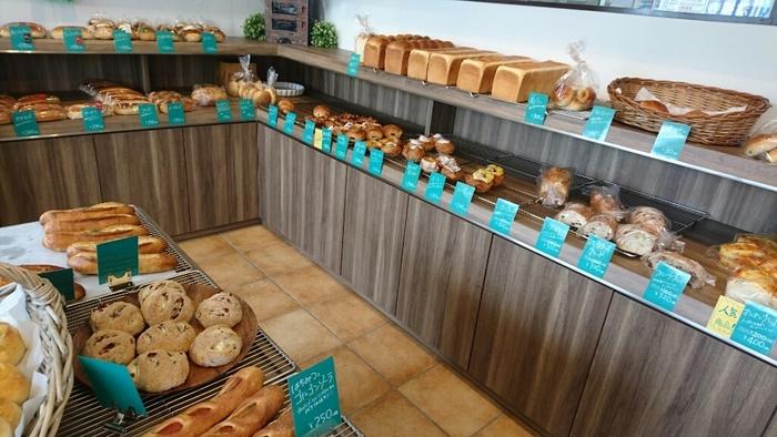木目調の明るい店内には、溶岩窯で焼き上げた、惣菜パン、菓子パン、テーブルパンなど豊富なメニューが揃っています。1年前のオープンから約130種類を越すパンを考案してきたそう。あれこれと目移りする幸せな時間を過ごせます。