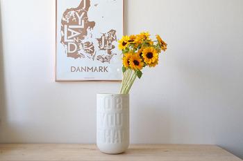 片側にひまわりのお花を寄せて。白い陶器に文字が入った花器は、さりげないアクセントにもぴったりですね。
