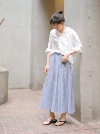 繊細なプリーツスカートを合わせれば、ビッグシャツもしおらしい表情にシフト。シューズはビーチサンダルでハズしてみるのが小粋です。