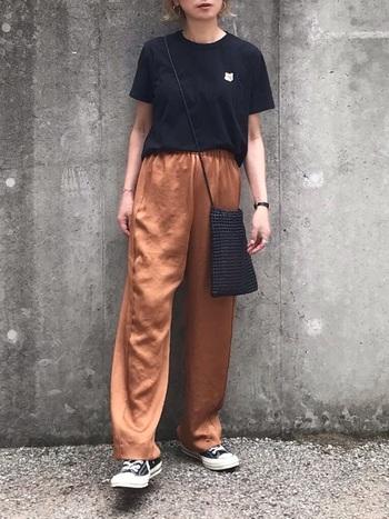 メゾンドキツネの小さなワンポイントが効いた黒Tシャツ。光沢感のあるサテンパンツを合わせることでカジュアルになりすぎない印象に。