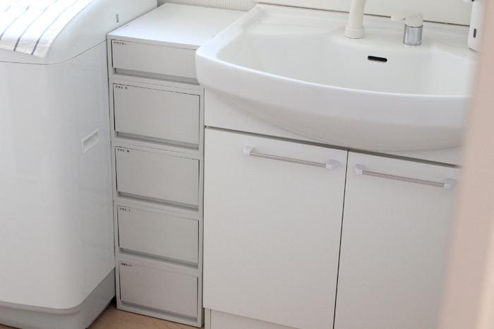 洗濯機と洗面台の間にできたすき間を有効に活用したアイデア。洗面所で使うドライヤーやタオルなどの洗面グッズを、スリムな引き出し収納にまとめています。