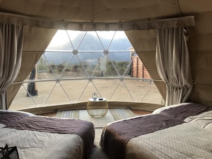 テントのカーテンを開けると、妙義山の雄大な姿が目の前に・・・!  こちらの「ラグジュアリーテント」では、絶好の立地。ベッドに身を横たえながら妙義山の風景を味わうことができますよ。
