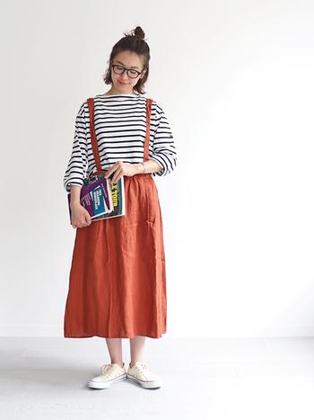 サスペンダー付きのスカートはボーイッシュで好印象なカジュアルコーデに。ほっこりとしたオレンジカラーや、トップスのゆるっとしたデザインがラフで親しみやすい雰囲気を演出します。