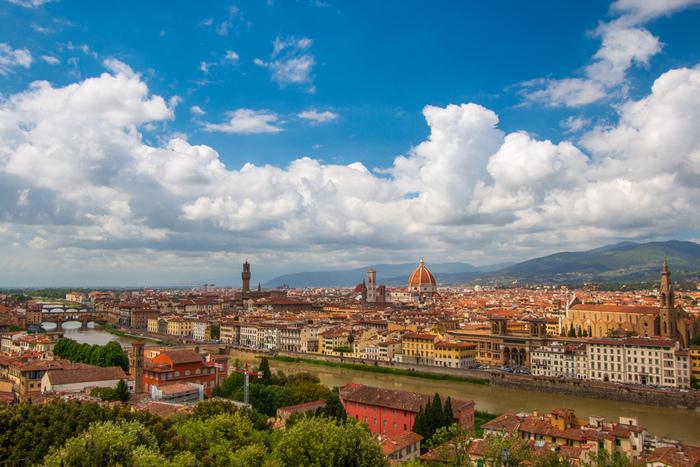"""ルネサンスを象徴する壮麗な大聖堂、オレンジ色の屋根が続く古い街並み、アルノ川にかかるポンテ・ヴェッキオ…。 今もなお中世以来の美しい景観を守り続け、""""花の都""""と称されるイタリアの古都「フィレンツェ」。 街の中心部は「フィレンツェ歴史地区」としてユネスコの世界遺産に登録され、世界中から多くの観光客が訪れます。 かつて商業や金融業の中心地として栄えたフィレンツェには、レオナルド・ダ・ヴィンチ、ミケランジェロ、ボッティチェリなど偉大な芸術家たちが集まり、中世にはルネサンス文化の中心地としても発展しました。"""