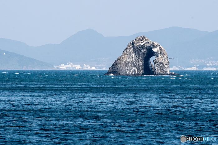 島の東の海上にそそり立った玄武岩のユニークな岩。高さが20mもあり、中央に波で浸食された大きな穴が開いています。めがねのように見えることから、通称めがね岩と呼ばれ、平成18年には県の指定文化財になりました。ダイナミックな光景に目を奪われます。
